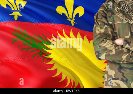 Crossed arms soldier with national waving flag on background - Guadeloupe Military theme. - Stock Photo