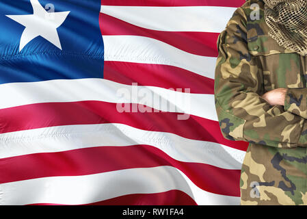 Crossed arms Liberian soldier with national waving flag on background - Liberia Military theme. - Stock Photo
