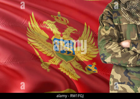 Crossed arms Montenegrin soldier with national waving flag on background - Montenegro Military theme. - Stock Photo