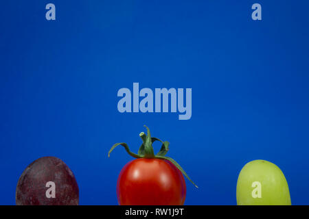 One cherry tomato red and green grapes on a blue background viewed in close-up - Stock Photo