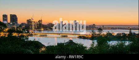View from Kings Park during twilight looking east over the Narrows bridge along the Swan River and Perth's foreshore - Stock Photo