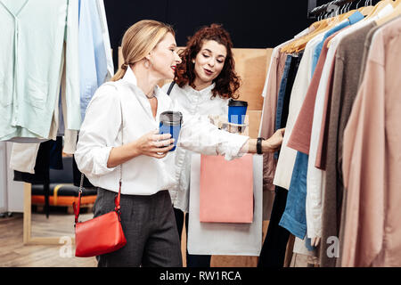 Daughter giving advice for her mother looking for new clothes Stock Photo