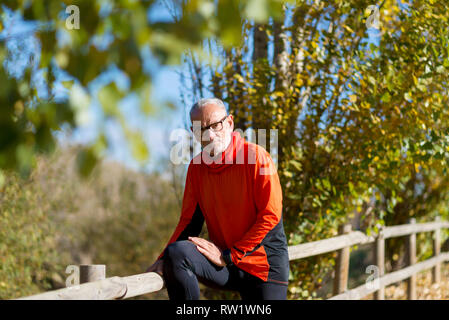 Front view of one senior runner man with sportswear sitting on a wooden fence while looking camera - Stock Photo