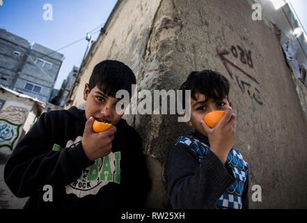 Gaza, Palestine. 4th Mar 2019. Palestinians kids are seen eating an orange near their home at the Jabalya refugee camp in the northern Gaza Strip. With high rates of unemployment and lack of job opportunities in Gaza, an increasing number of families are facing poverty after losing work during the last 12-year blockade on Gaza. Credit: SOPA Images Limited/Alamy Live News - Stock Photo