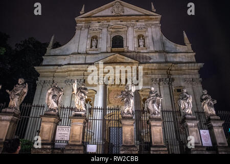 Exterior facade of Saints Peter and Paul Church at night with a line of stone statues of various saints, Krak—w, Lesser Poland Voivodeship, Poland. - Stock Photo