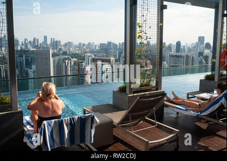 12.02.2019, Singapore, Republic of Singapore, Asia - Hotel guests are looking at the cityscape while sunbathing on the terrace by the rooftop pool. - Stock Photo