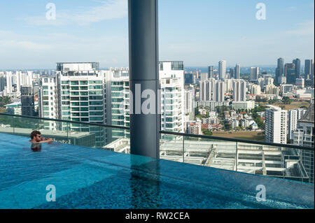 12.02.2019, Singapore, Republic of Singapore, Asia - A hotel guest is looking at the downtown cityscape from the poolside of a rooftop swimming pool. - Stock Photo