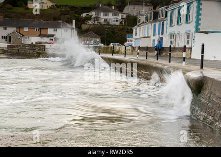 Editorial: People & Logos. Portmellon, Mevagissey, Cornwall, UK. 03/03/2019. Large swells kicked up by storm Freya crash against the sea defences. - Stock Photo
