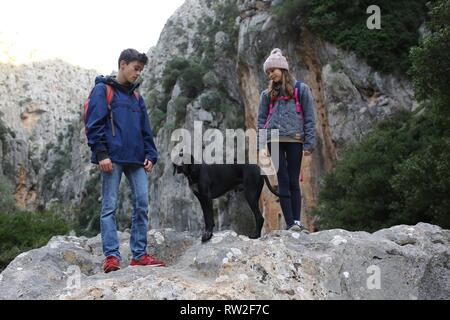 Children hiking with dog in mountain landscape, outdoor adventure - Stock Photo