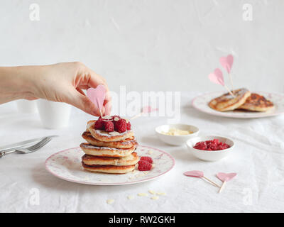 Breakfast table with a stack of pancakes, heart decor and a hand placing raspberries - Stock Photo