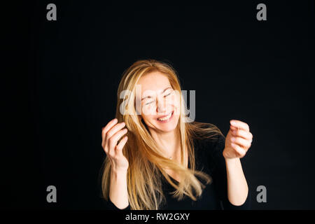 Close up studio portrait of a beautiful woman in the black dress, laughing, eyes closed, against the black background - Stock Photo