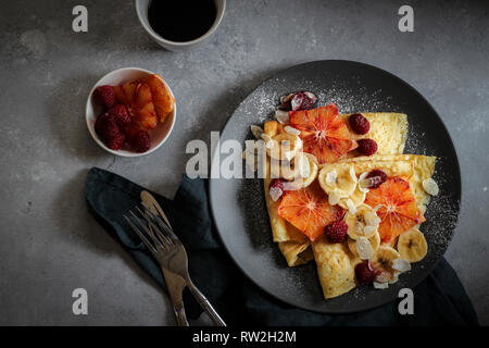 Crepes with bananas, blood orange slices and raspberries on a dark background - Stock Photo