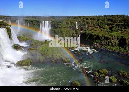 Gorgeous Rainbow over the Powerful Iguazu Falls at Brazilian Side with Many Visitors on the Boardwalk, Foz do Iguacu, Brazil, South America - Stock Photo