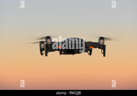 Drone Close-up in front of magical sunset sky - Stock Photo