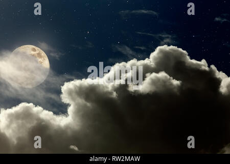Arising full moon over strong cloud in a starry night - Stock Photo