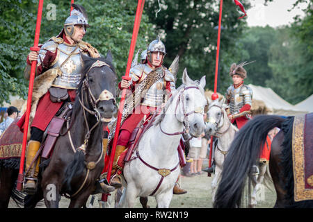Men dressed in medieval costumes and armour carry lances in their hands as they ride horseback at the annual St John's Fair - Jarmark Świętojański -   - Stock Photo