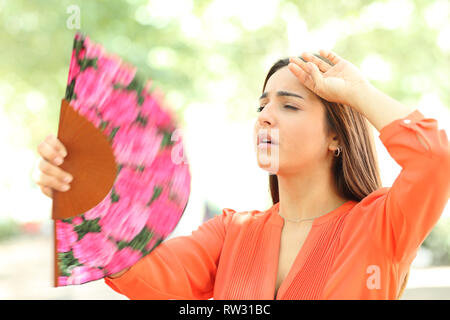 Overwhelmed girl suffering heat stroke fanning in the street in summer - Stock Photo