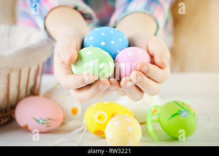 Happy Easter. Congratulatory easter background. The child holds Easter eggs in hand. Selective focus. - Stock Photo
