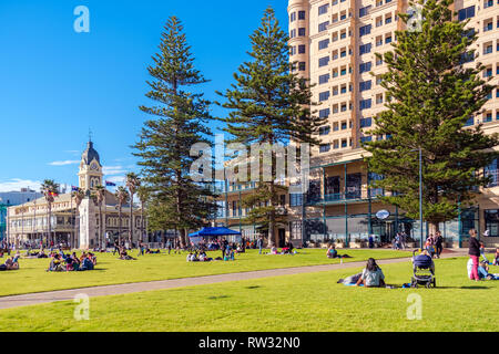 Adelaide, Australia - August 13, 2017: People sitting on green grass and enjoying warm winter day in Glenelg - Stock Photo