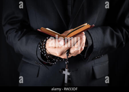 Hands of a christian priest dressed in black holding a crucifix and reading New Testament book. Religious person studies Bible and holds prayer beads, - Stock Photo