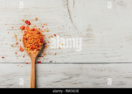 Spoonful of crushed red chili pepper over wooden background - Stock Photo