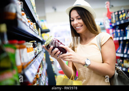 Smiling happy woman doing shopping in supermarket - Stock Photo