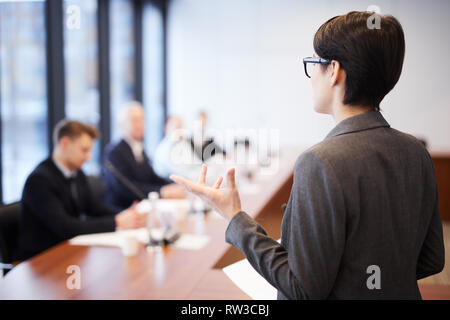 Back view portrait of young businesswoman giving speech in conference room and gesturing, copy space