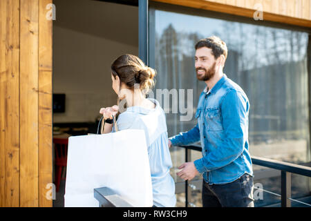 Young couple entering home carrying shopping bags. Happy purchase and modern living concept