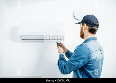 Repairman in blue workwear serving the air conditioner controling with remote on the white wall background - Stock Photo