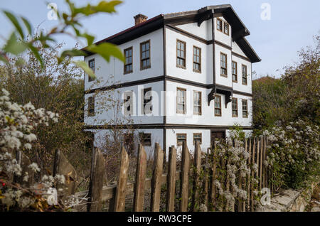 Traditional Ottoman House from Kastamonu in Turkey.Wooden three storey house surrounded by fences inside and around the garden. - Stock Photo