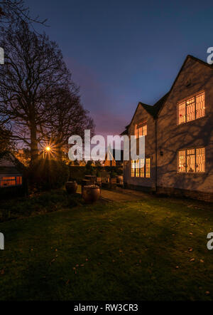 A house at night with lights on in England. - Stock Photo