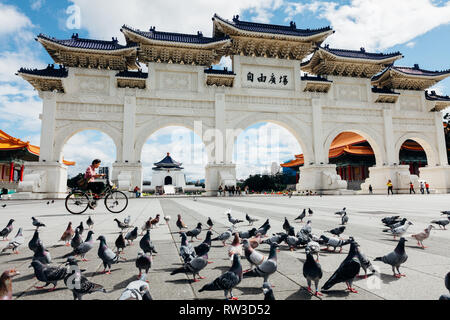 Taipei, Taiwan - November 06, 2018: Woman rides a bicycle in front of the National Chiang Kai-shek Memorial Hall on November 06, 2018 in Taipei, Taiwan​ - Stock Photo