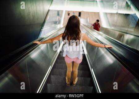 Young Girl going down the escalator, London Underground, 'The Tube' silver background - Stock Photo