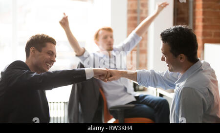 Happy businessmen workers giving fist bump celebrating team project success - Stock Photo
