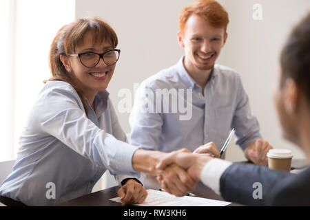 Smiling female middle aged hr manager handshaking hiring male applicant - Stock Photo