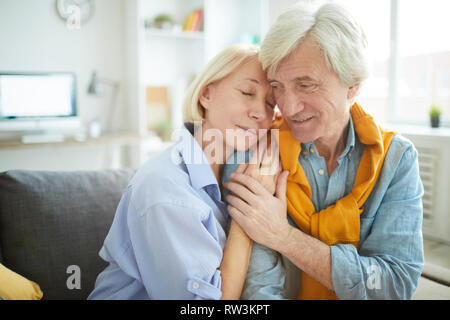 Portrait of mature couple in love embracing tenderly at home , copy space - Stock Photo