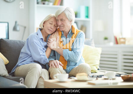Portrait of mature couple in love embracing tenderly sitting on sofa at home , copy space - Stock Photo