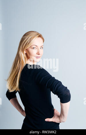 Close up studio portrait of a beautiful woman in the black dress against white background - Stock Photo