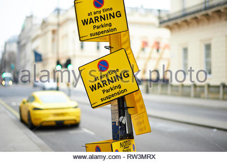Yellow car illegally parked on parking suspended bay in London - Stock Photo