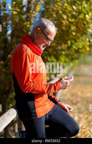 Side view of a senior runner man leaning on fence while testing exercise in a mobile phone outdoors in a sunny day - Stock Photo