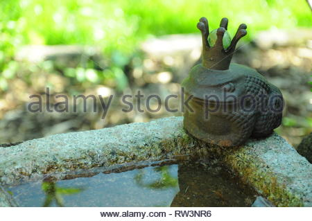 Decorative frog with crown on bird bath - Stock Photo