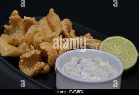deep fried anchovies with tartar sauce and lime wedge in a serving dish - Stock Photo