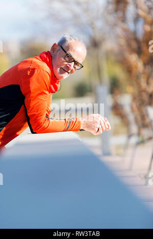 Front view of a senior runner man with sportswear sitting on a wooden fence while looking camera - Stock Photo