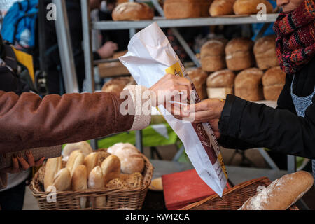 Bread being purchased from a farmers market bakery stall in Edinburgh, Scotland - Stock Photo