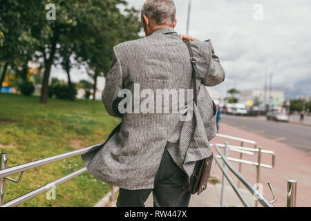 An gray hair elderly man in a gray jacket with an umbrella under his arm and a leather brown bag on his shoulder rushing down the street. Back view - Stock Photo