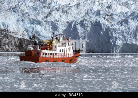 Red cruise boat among the icebergs in Greenland. Boating in front of Eqip Sermia glacier in the frozen sea - Stock Photo