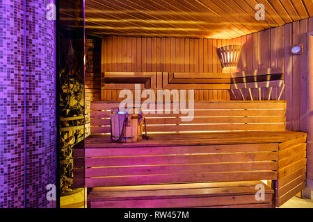 Interior of wooden finnish sauna with birch broom, bucket and stove. The Finnish sauna is a substantial part of their culture. - Stock Photo