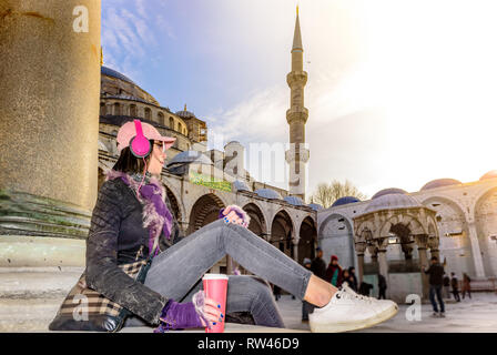 Beautiful woman in hat with takeaway coffee sunglasses,headphones sits at courtyard of Sultanahmet Mosque or Blue Mosque in Istanbul,Turkey - Stock Photo