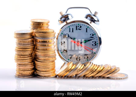 A lot of euro coins in front of an alarm clock isolated on white. - Stock Photo