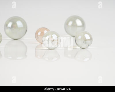 Glass marbles on a grey surface. beautiful reflection, abstract background - Stock Photo